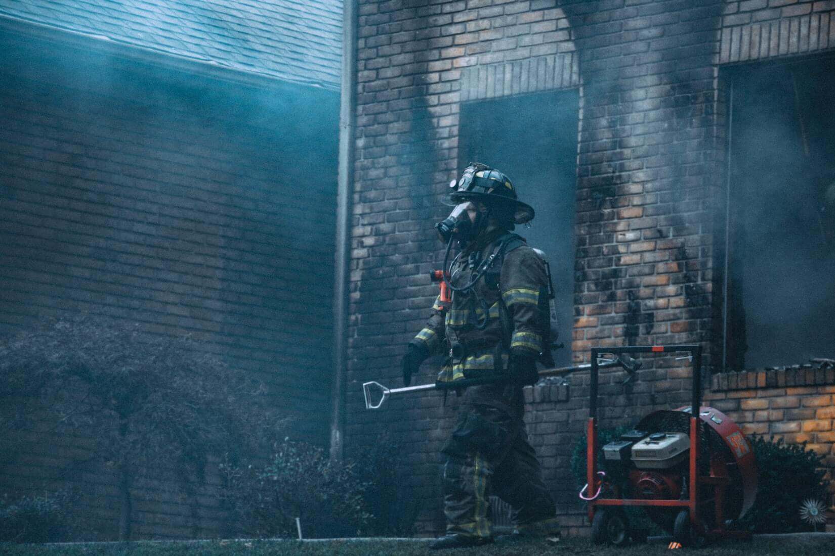 Firefighter outside fire damaged property