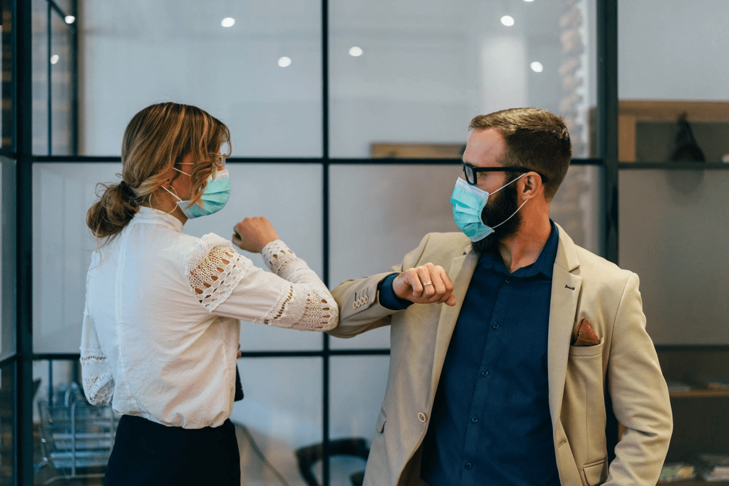Two colleagues elbow bump, whilst wearing face masks