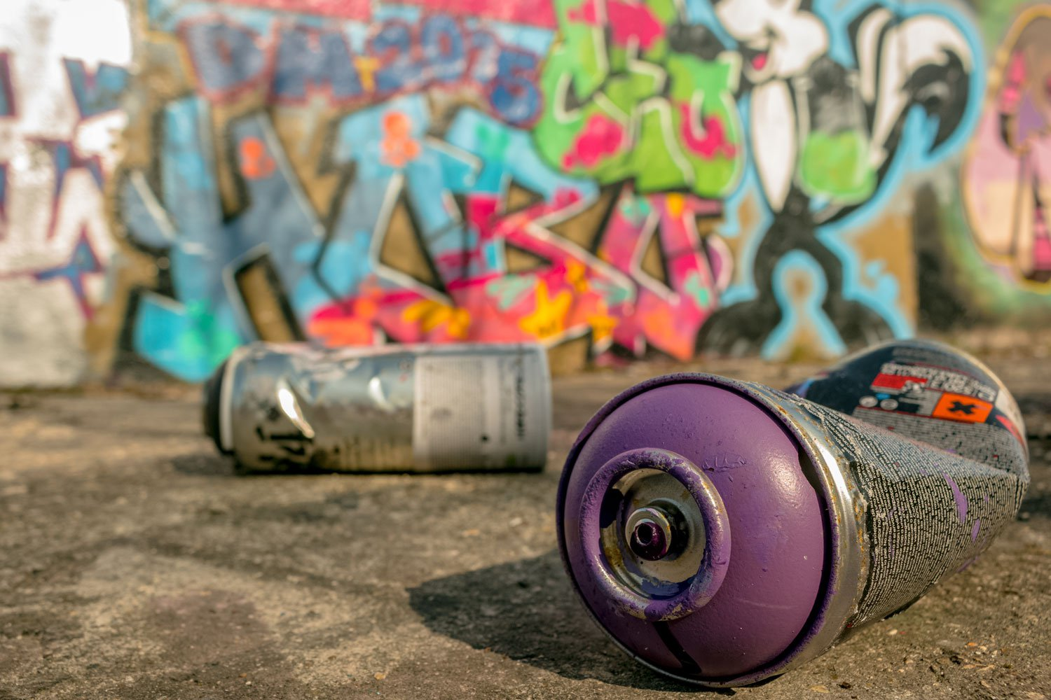 Discarded spray pain cans in front of graffiti