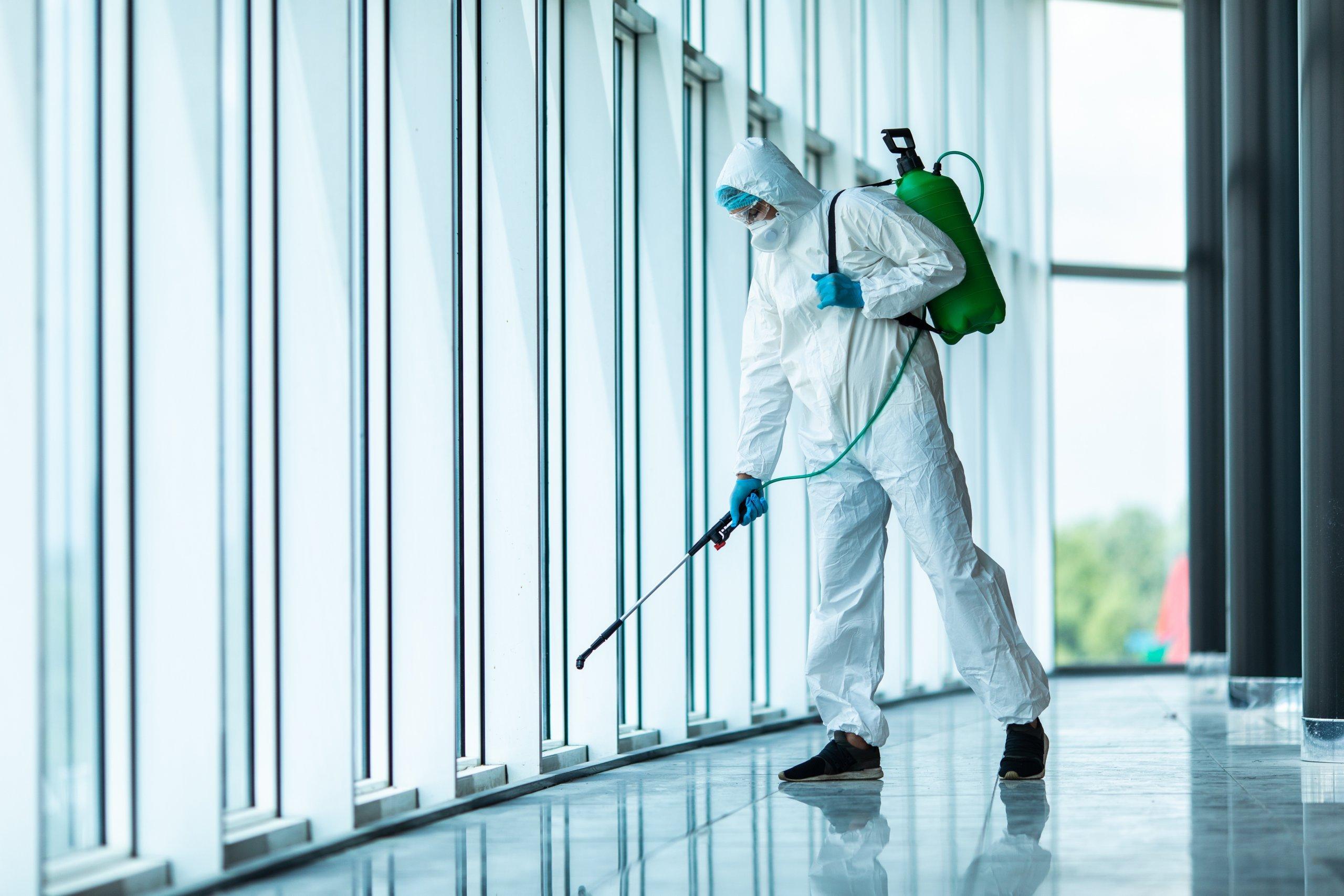 Man in full PPE sanitising room