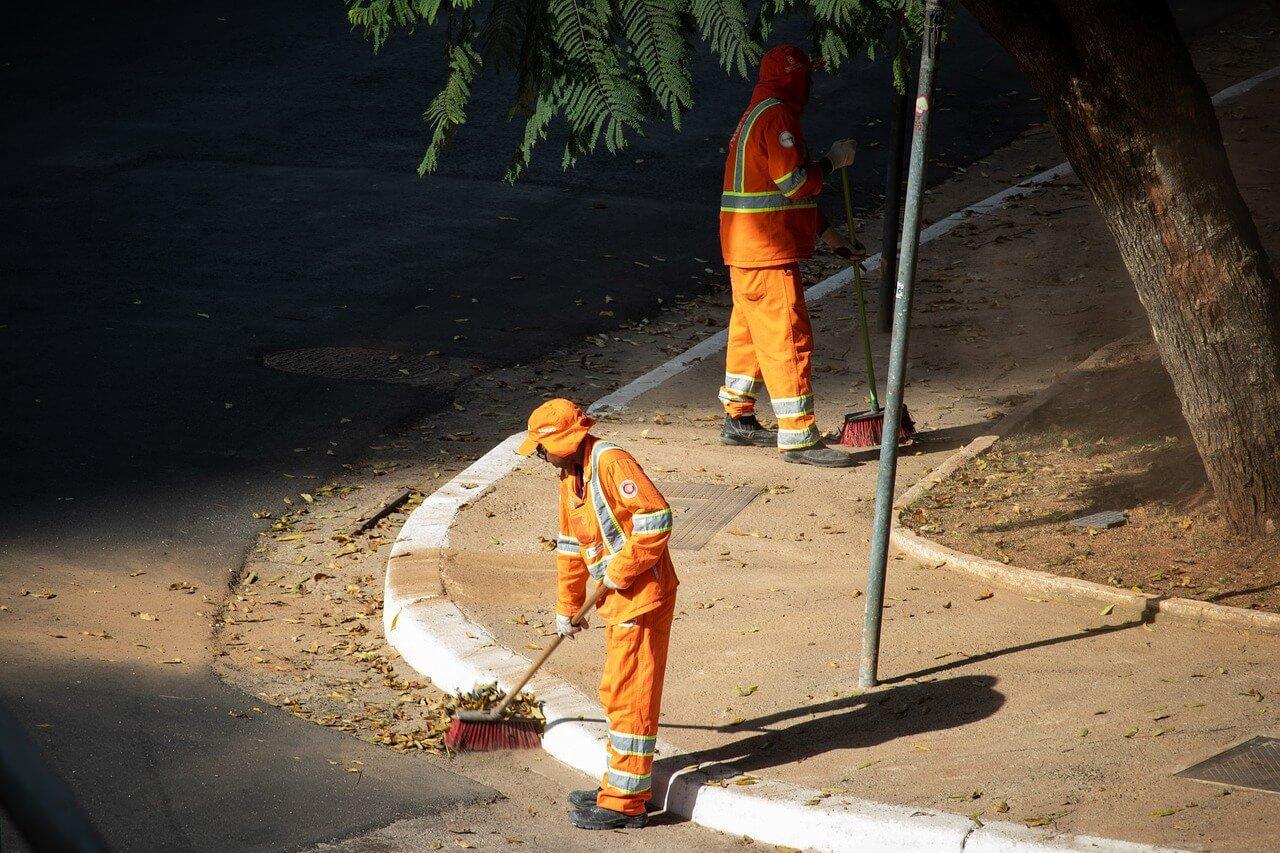 Two men road sweeping in hi-vis
