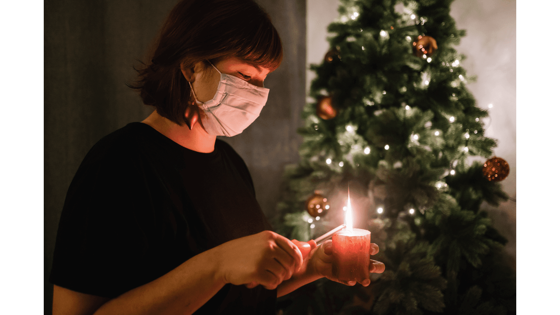 Woman in face mask lighting a candle in front of a Christmas tree