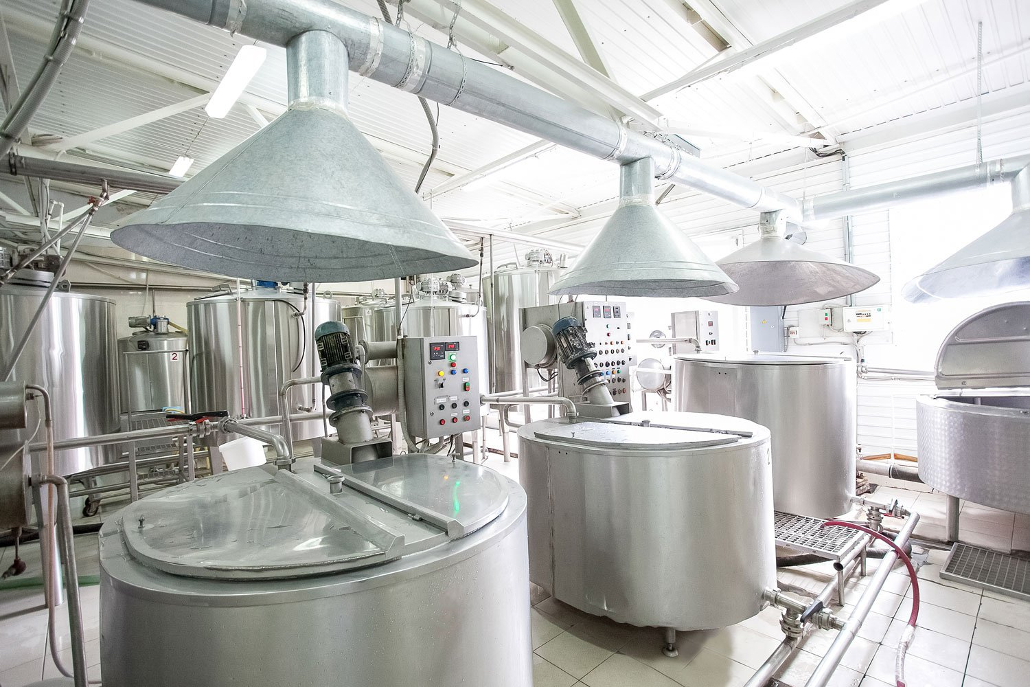Food production facility with large metal vats and overhead ventilation