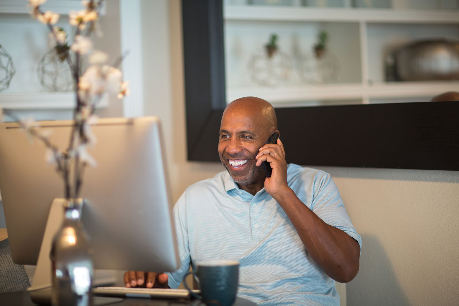 Man smiling whilst on the phone from his home office